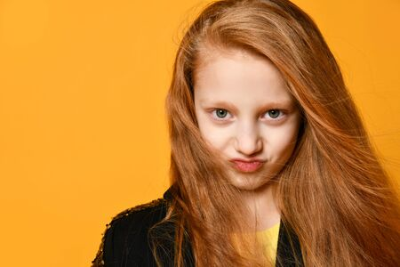 Angry Red-haired teenage kid in black jacket. She is smiling and looking at you, posing against orange studio background. Sincere emotions, fashion, beauty. Close up, copy space