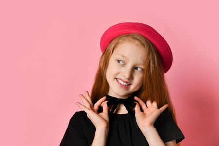 Ginger teenage child in black dress, checkered shirt on waist, red hat. She smiling, holding her choker, posing against pink studio background. Hipster style, fashion, beauty. Close up, copy space