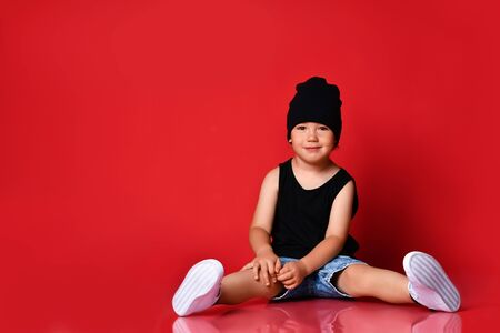 Small positive boy in stylish casual clothing, cap and white sneakers sitting on floor and smiling over red wall background. Trendy children clothing and happy childhood concept