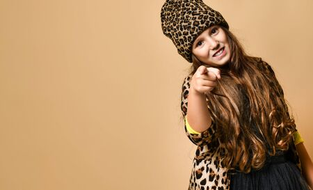 Young plus size girl model in stylish leopard colored casual clothing and black skirt standing and pointing at camera over yellow wall background. Copy space in left side