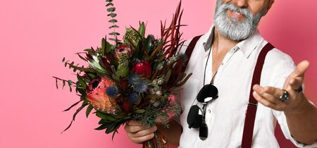 Stylish middle-aged bearded man with a modern haircut and fashionably dressed holds a bouquet of flowers. The guy holds out his hands in the frame - says hello. Valentines day concept
