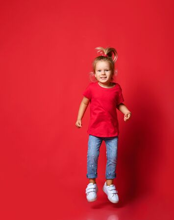 Small happy excited blond girl in stylish casual clothing and white sneakers jumping over red wall background. Trendy children clothing and happy childhood concept