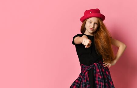 Red-haired teenage child in black dress, checkered shirt on her waist, red hat. She pointing at you while posing against pink studio background. Hipster style, fashion, beauty. Close up, copy space Stockfoto