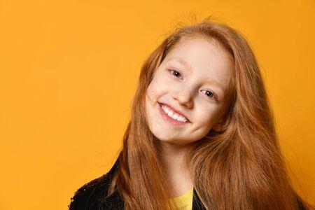 Adolescent aux cheveux roux en veste noire. Elle sourit et vous regarde, posant sur fond de studio orange. Émotions sincères, mode, beauté. Gros plan, espace de copie