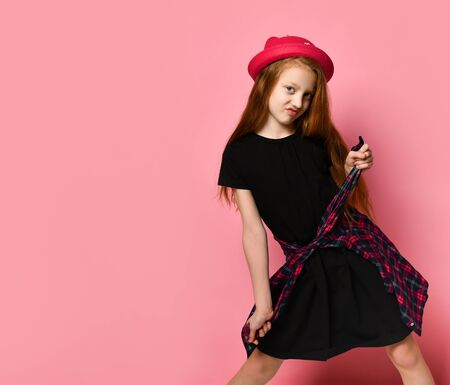 Red-haired teenage kid in black dress and red hat. She tightens checkered shirt on her waist while posing against pink studio background. Hipster style, fashion, beauty. Close up, copy space