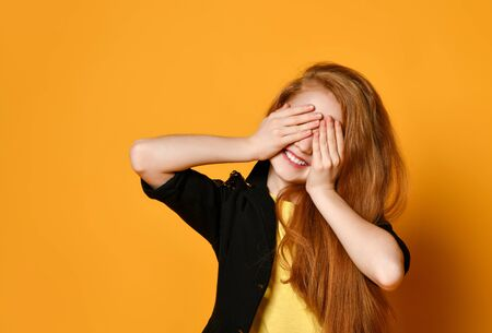 Red-headed teenage child in black jacket and yellow t-shirt. She is smiling, closed her eyes with palms, posing on orange studio background. Sincere emotions, fashion, beauty. Close up, copy space Stockfoto