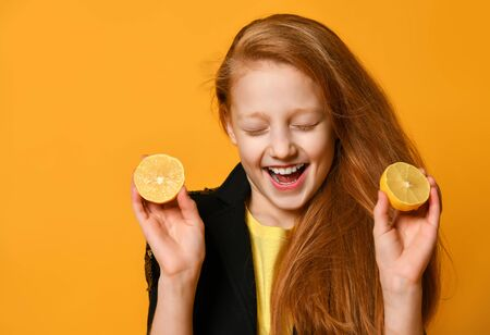 Red-haired teenage girl in black jacket and yellow t-shirt. She is smiling with closed eyes, holding two halves of lemon, posing on orange background. Emotions, fashion, beauty. Close up, copy space