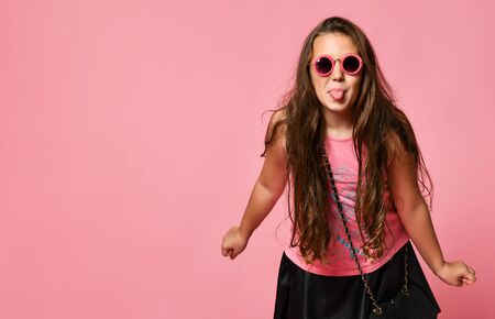 Young happy plus size girl model with long hair in stylish summer casual clothing and sunglasses showing tongue and feeling playful over pink background. Trendy summer youth clothing concept