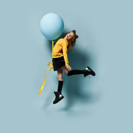 Ginger teenager with fancy hairstyle in yellow sweatshirt, black skirt, knee-highs, boots. Smiling, holding balloon, jumping up against blue background. Hipster style, fashion, holiday. Full length Stockfoto