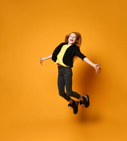 Red-headed teen female in black jacket, pants and boots, yellow t-shirt. She is smiling, jumping up with spreaded hands, posing on orange background. Sincere emotions, fashion. Full length, copy space