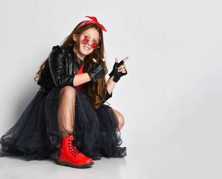 Young smiling girl in bright rock style clothing, red boots and accessories sitting on floor with and pointing up with fingers over white background. Trendy youth casual fashion concept