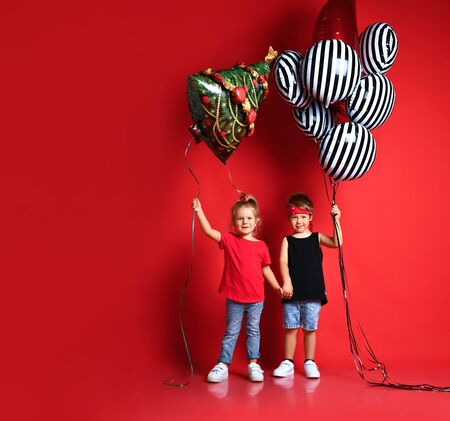Full length shot of little girl and boy, in stylish clothes, looking at camera, smiling, holding striped balloons and another one in form of Christmas tree, posing in red studio. Kids fashion