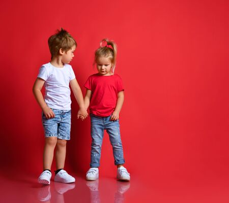 Small happy children boy and girl in stylish casual clothing standing, holding hands and feeling shy over red background. Trendy children clothing, happy childhood and friendship concept Stockfoto
