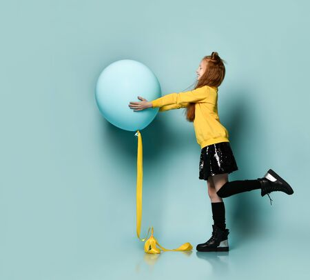 Ginger teenage kid with fancy hairstyle in yellow sweatshirt, black skirt, knee-highs, boots. Smiling, holding balloon, posing sideways on blue background. Hipster style, fashion, holiday. Full length