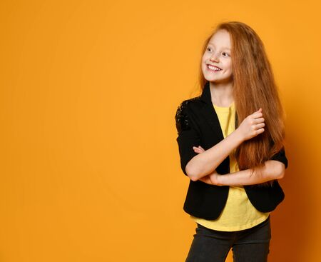 Ginger teen female in black jacket and pants, yellow t-shirt. She is smiling, hands folded, posing against orange studio background. Sincere emotions, fashion, beauty. Close up, copy space