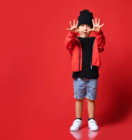 Small positive boy in red jacket and cap standing and showing all his fingers over red wall background. Trendy children clothing and happy childhood concept Stockfoto