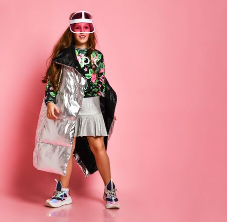Young happy teen girl in stylish floral printed casual clothing, metallic coat, sneakers and modern accessories standing over pink wall background and smiling. Trendy youth clothing concept