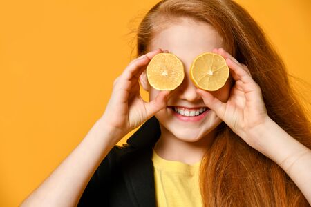 Red-haired schoolgirl in black jacket and yellow t-shirt. She is smiling, put two halves of lemon at her eyes, posing on orange background. Sincere emotions, fashion, beauty. Close up, copy space