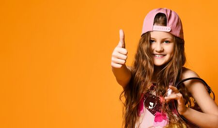 portrait of a cute little teen girl showing a thumb sign a yellow studio wall. Childrens fashion concept