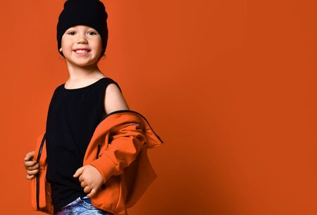 cute little lad, dressed in a black cap and stylish red jacket, boy tooks off his jacket and smiled at the camera, against a orange background