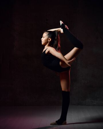 little girl in a black gymnastics leotard gymnast performs an exercise. Balance on one leg with a grip. Sport concept, gymnastics, fitness. Isolated on dark background. Stockfoto