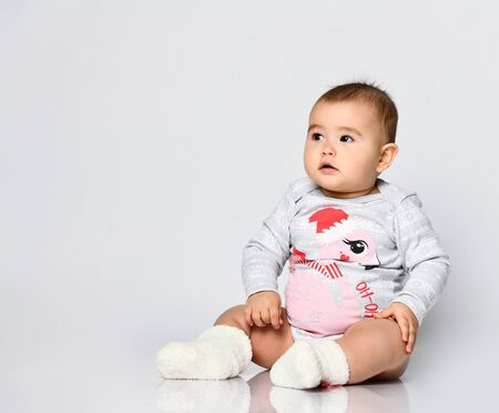 Little kid in socks and gray bodysuit with christmas flamingo print. She is sitting on the floor isolated on white. New Year, holidays. Articles about childhood or advertising for babies. Close up
