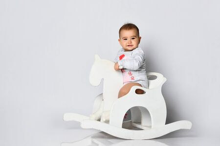 Toddler in gray bodysuit with christmas flamingo print. She is riding a rocking horse isolated on white. New Year, holidays. Concept for articles about childhood or advertising for babies. Close up