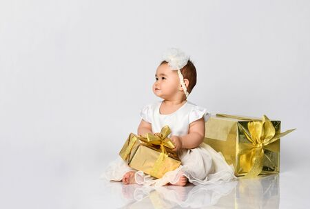 Little babe in dress and headband, barefoot. She posing with two golden gift boxes, sitting on floor isolated on white. Christmas, New Year, birthday. Childhood, advertising for babies. Close up