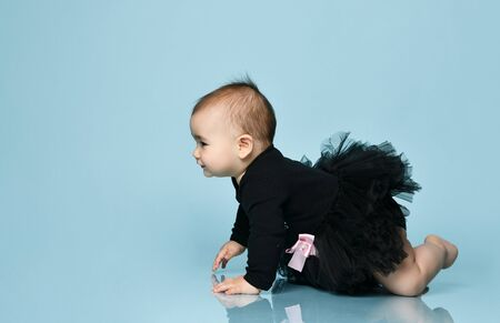 Toddler in black bodysuit with pink bow, poofy skirt, barefoot. She creeping on floor against blue studio background. Articles about childhood, advertising for babies. Copy space, side view, close up