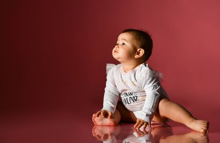 Chubby kid in white bodysuit with inscription, barefoot. She pulling her hands to someone, sitting on floor against pink background. Christmas, New Year, holidays. Advertising for babies. Close up