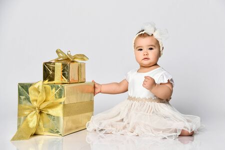 Baby girl in dress and headband, barefoot. She holding golden gift box tied with ribbon, sitting on floor isolated on white. birthday party. Childhood, advertising for babies. Stockfoto