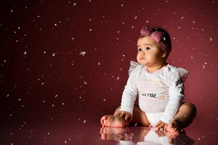 Little kid in a headband and smart white bodysuit with inscription, barefoot. She looking at snowflakes, sitting on floor against pink background. New Year, holidays. Childhood, advertising. Close up