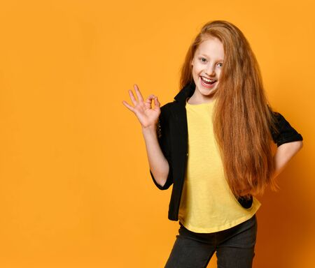 Ginger teenage girl in black jacket and pants, yellow t-shirt. She is smiling, showing okay sign by her hand posing on orange studio background. Sincere emotions, fashion, beauty. Close up, copy space
