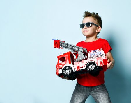 Positive boy in bright stylish casual clothing and sunglasses standing and holding toy fire engine in hands over blue background. Trendy children clothes, holiday gift, party concept
