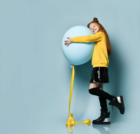 Ginger teenage child with fancy hairstyle, in yellow sweatshirt, black skirt, knee-highs, boots. Smiling, hugging balloon, posing sideways on blue background. Hipster, fashion, holiday. Full length