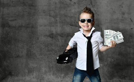 boy little businessman in white shirt, jeans, tie and sunglasses standing and holding black toy car present and dollars cash over grey background. Trendy children clothes, holiday gift concept