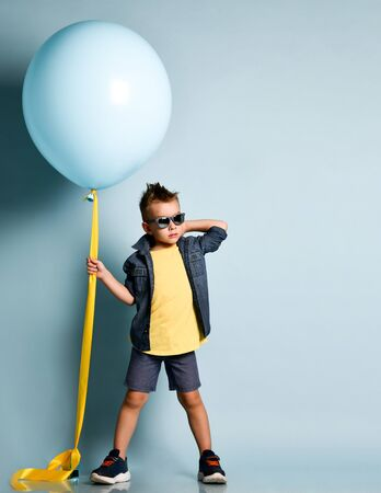 Blond boy in stylish casual clothing, sneakers and sunglasses standing near blue air balloon and looking at camera over blue background. Trendy children clothes, holiday, party concept