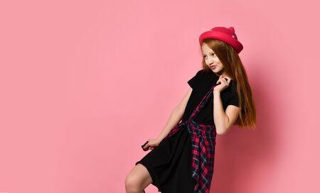 Adolescente rousse en robe noire et chapeau rouge. Elle resserre la chemise à carreaux sur sa taille, posant sur fond de studio rose. Style hipster, mode, beauté. Gros plan, espace de copie