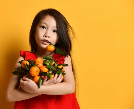 Little Asian girl in a red blouse holds a manlarink with her teeth. He looks surprised, holds fruit in his hands with green leaves, posing on an orange background. Childhood, fruits, emotions. Close copy space