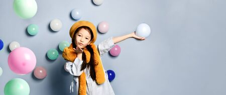 Little brunette asian child in oversized shirt dress, brown beret and scarf. She sending air kiss, posing with multicolored balloons against blue background. Fashion, hipster style. Foto de archivo