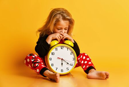 Little blond girl in red dotted pajamas sitting on floor with big alarm clock and feeling tired over yellow background. Different times of day and children schedule concept
