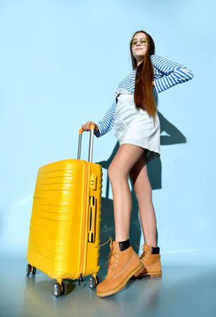 Brunette teenager in jeans overall skirt, striped sweatshirt, sunglasses and boots. She smiling, posing with yellow suitcase, blue background. Hipster style, fashion, beauty. Copy space. Full length