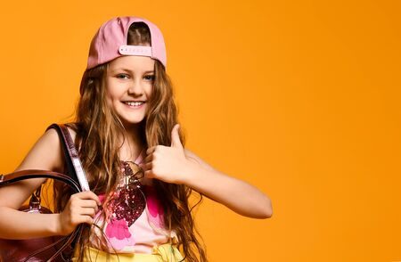 portrait of a cute little teen girl showing a thumb sign a yellow studio wall. Children's fashion concept