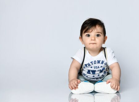 Little child in t-shirt with inscriptions, jeans with suspenders and booties. He is looking wondered, sitting on floor isolated on white. Articles about childhood or advertising for babies. Close up
