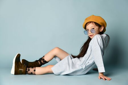 Little brunette asian guy in sunglasses, shirt dress, brown beret, boots. Smiling toothless smile, posing while sitting sideways on the floor on a blue background. 版權商用圖片