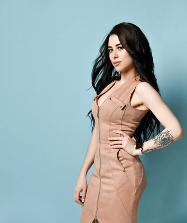 Spectacular brunette with long curly hair in a beige suede dress. There is a watch on her tattooed arm. Standing sideways pose against a blue studio background. The concept of beauty and fashion.