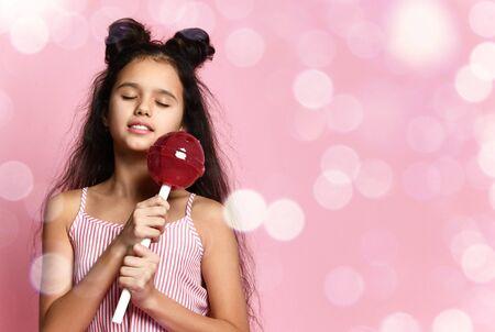 Adolescente brune avec une coiffure fantaisie, en robe rayée. Elle sourit les yeux fermés, tenant une énorme sucette rouge tout en posant sur fond de studio rose avec bokeh. Mode, beauté, bonbons. Fermer