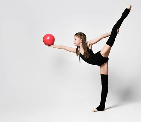Young girl gymnast in black sport body and uppers standing with raised leg and holding pink gymnastic ball in stretched hand over white background, top view. Rhytmhic gimnastics beauty cocnept