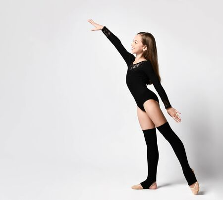 Artistic Gymnast of a little girl in a black sports body and long socks with leggings posing in a rack with outstretched arm on a light background. Rhythmic Gymnastics Beauty Concept