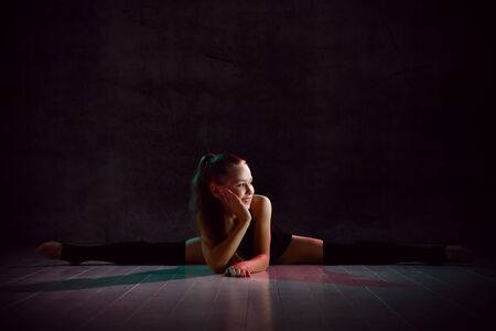 Young smiling girl gymnast in black sport body and uppers sitting in twine on floor and holding pink gymnastic ball in hands over dark background. Rhythmic gymnastics beauty concept Stock Photo
